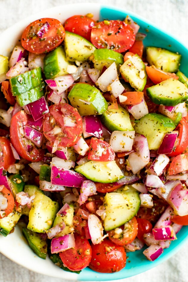 Cucumber tomato and red onion salad in a bowl and seasoned with herbs.