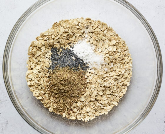 Mixing bowl with oats, flaxseed, poppyseeds and baking powder.