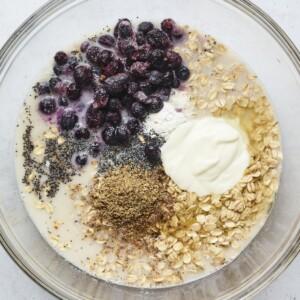 Mixing bowl with oats, milk, blueberries, yogurt, baking powder, flaxseed, lemon juice and poppyseeds.