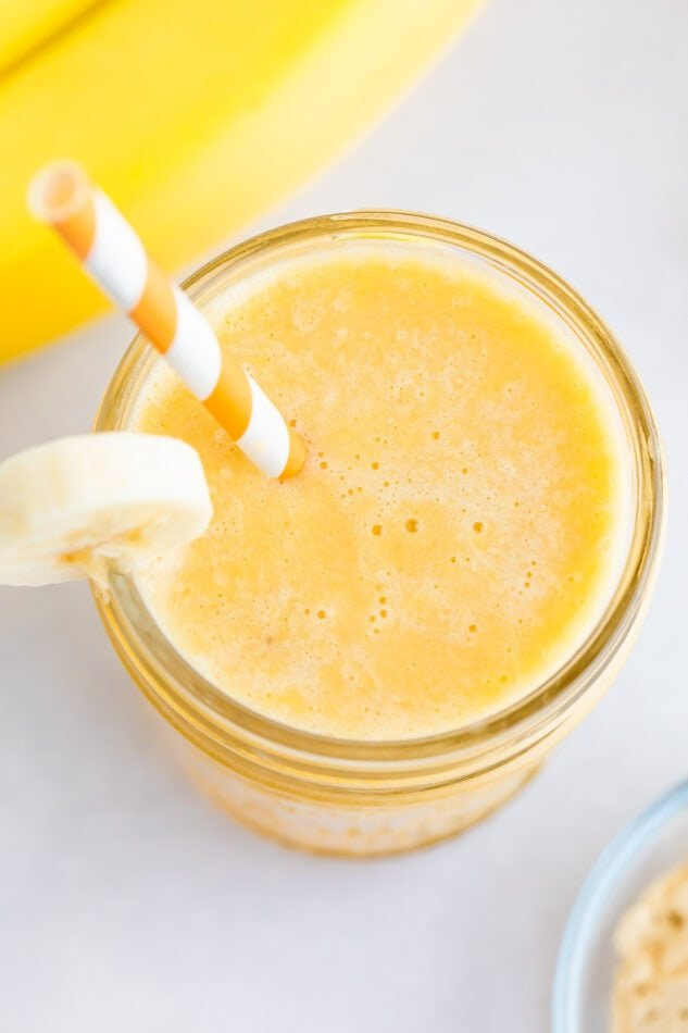 عصير موز البرتقال في وعاء زجاجي ، مزين بشريحة موز ويقدم مع قش ورقية مخططة باللونين البرتقالي والأبيض.