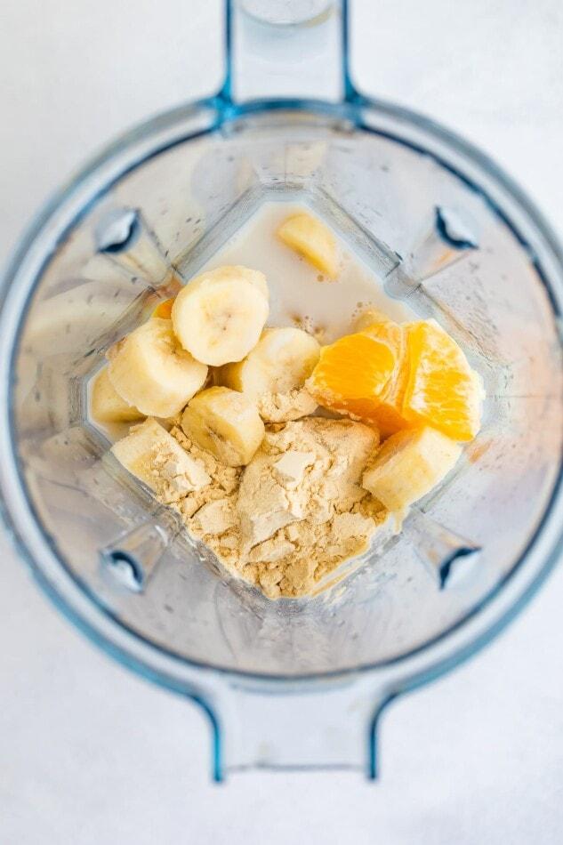 الحليب والموز ومسحوق البروتين والبرتقال في الخلاط.