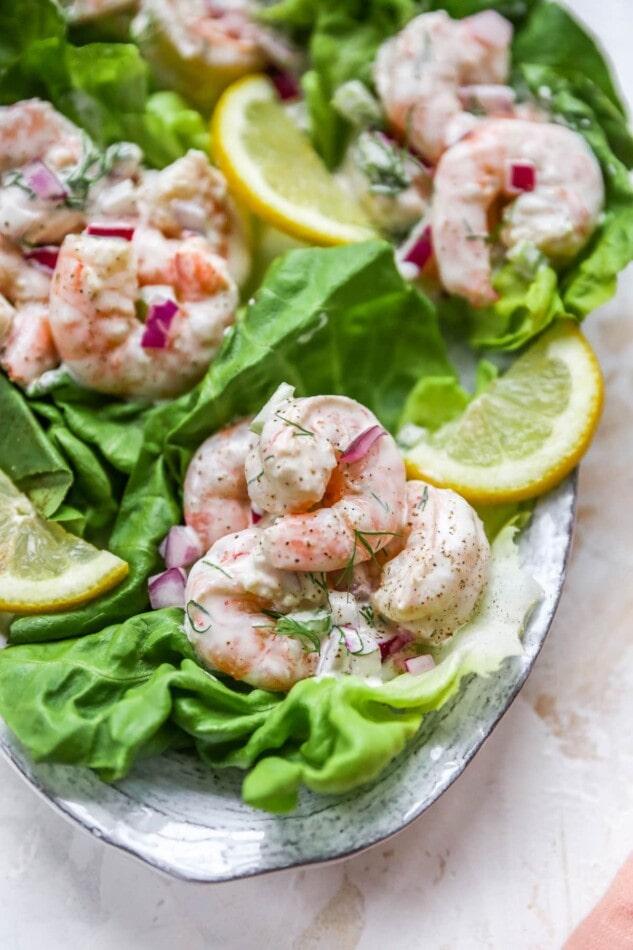 Shrimp salad served on lettuce cups. Lettuce cups are on a serving platter.