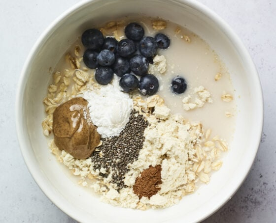 Bowl with blueberries, protein powder, cinnamon, almond milk, chia seeds, oats and almond butter.