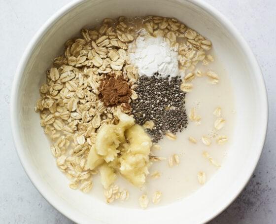 Mixing bowl with oats, almond milk, cinnamon, chia seeds, banana and baking powder.