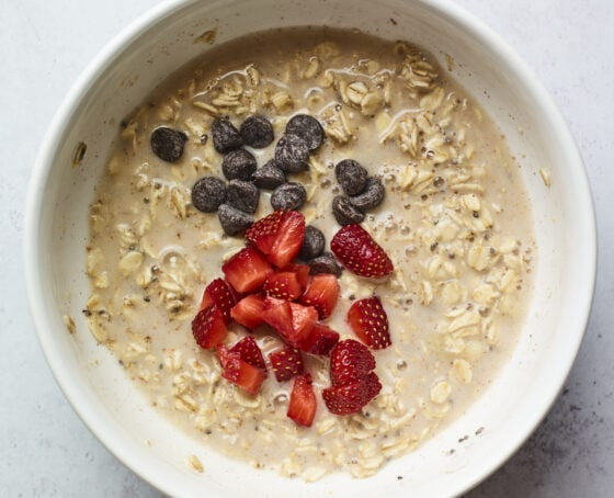 Mixing bowl with baked oatmeal mixture and chocolate chips and strawberries.