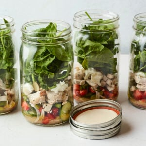 Four mason jars filled with a strawberry spinach chicken salad.