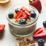 Jar of chia pudding topped with berries and granola. More granola and berries are scattered on the table around the jar.
