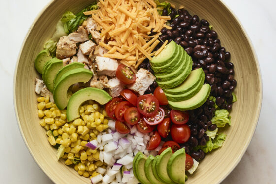 Salad bowl with corn, onion, avocado, tomato, bbq chicken, cheese, lettuce and black beans.