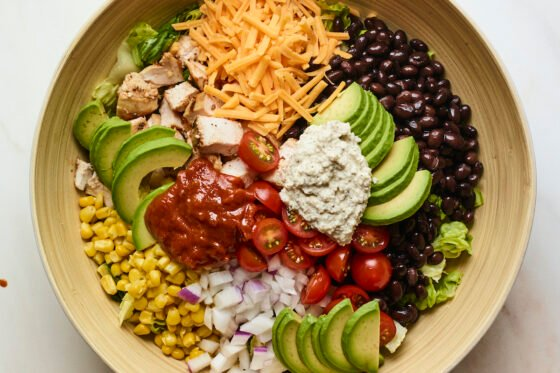 Salad bowl with corn, onion, avocado, tomato, bbq chicken, cheese, lettuce, ranch and black beans.