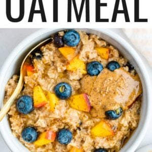 Blueberry peach oatmeal in bowl with blueberries and fresh chopped peaches on top with a little almond butter on top as well.