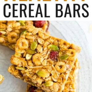 Cereal bars studded with dried cranberries and seeds on a plate.