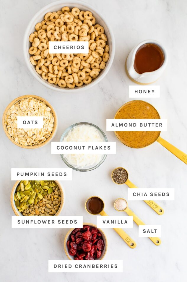 Ingredients for cereal bars laid out on a marble surface with labels.