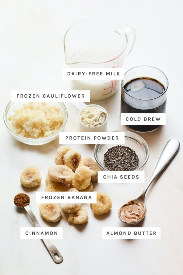 Milk, protein powder, cold brew, frozen banana and cauliflower, chia seeds, almond butter and cinnamon measured out.