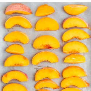 Frozen peach slices on a parchment paper lined cookie sheet.