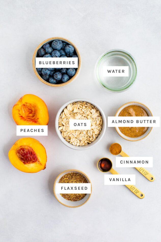Ingredients measured out to make blueberry peach oatmeal: blueberries, water, peaches, oats, almond butter, cinnamon, vanilla and flaxseed.