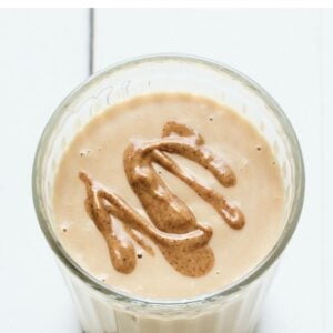 Peanut butter protein shake in a glass topped with a peanut butter drizzle.