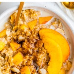 Peaches and cream oatmeal in a white bowl with fresh peaches and oat milk on top.