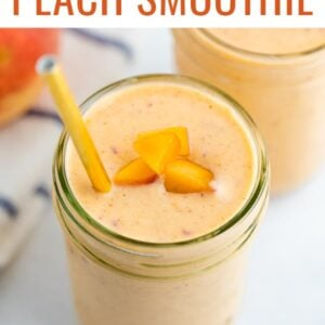Mason jar with a peach smoothie garnished with a gold straw and peach pieces.
