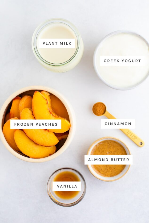 Ingredients measured out to make peach smoothies: plant milk, greek yogurt, frozen peaches, cinnamon, almond butter and vanilla.