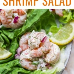 Shrimp salad served on a bed of lettuce and garnished with a slice of lemon.