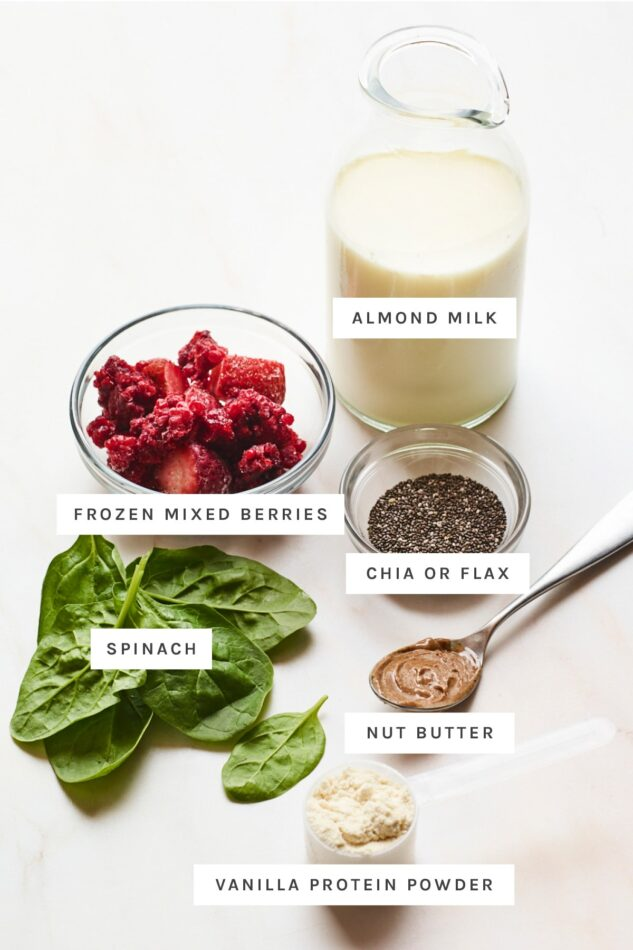 Almond milk, frozen berries, chia seeds, spinach, nut butter and vanilla protein powder measured out.