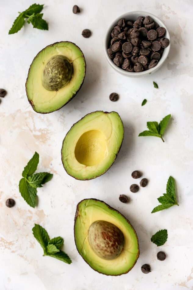 Avocados, mint leaves and chocolate chips on a table top.
