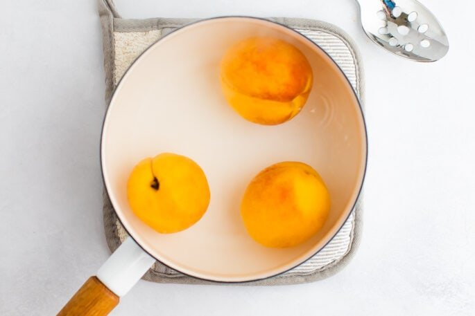 Three peaches in a white pot with water.