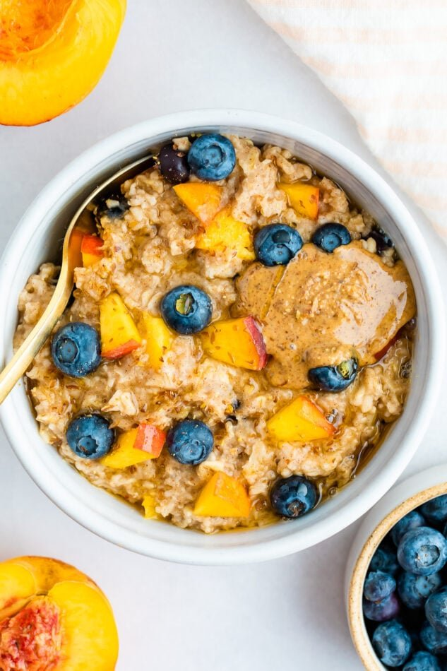 Overhead shot of blueberry peach oatmeal in a white bowl with blueberries and fresh chopped peaches on top with a little almond butter on top as well.