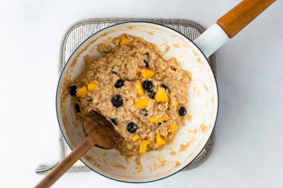 White saucepan with cooked blueberry peach oatmeal.