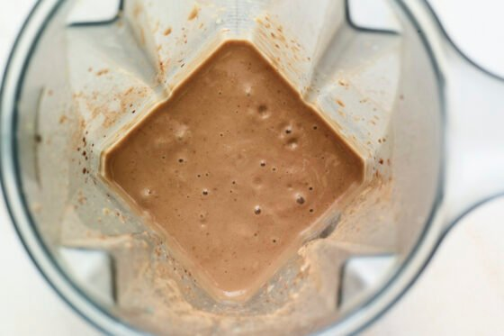 Blended chocolate protein shake in a blender.