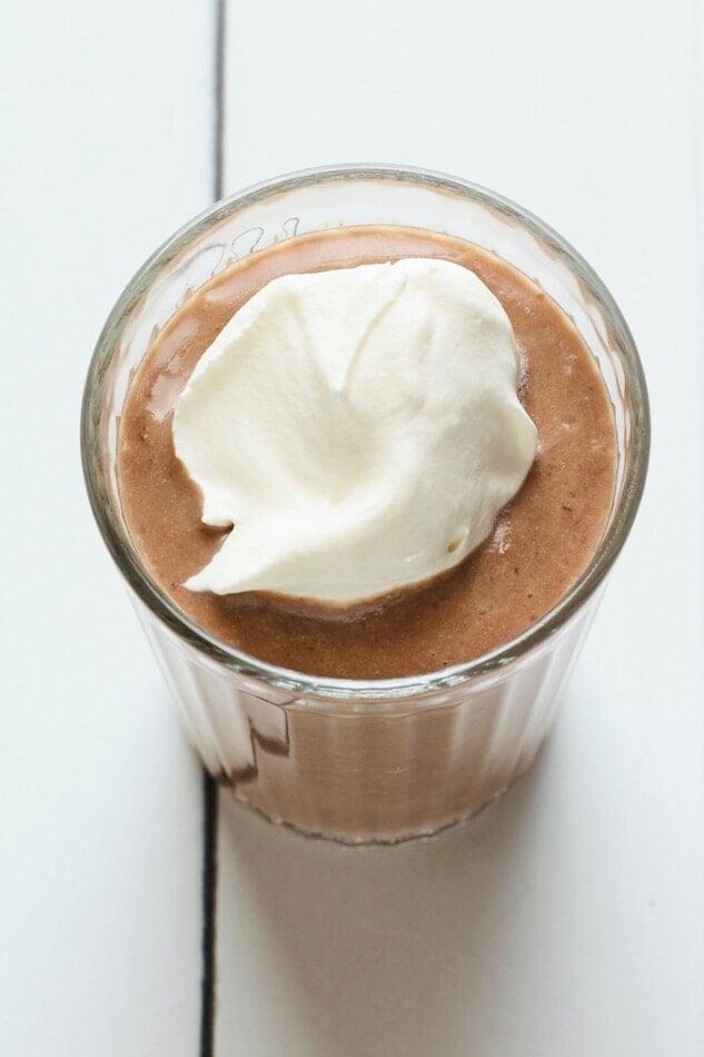 مخفوق بروتين الشوكولاتة في كوب مغطى بالكريمة المخفوقة.