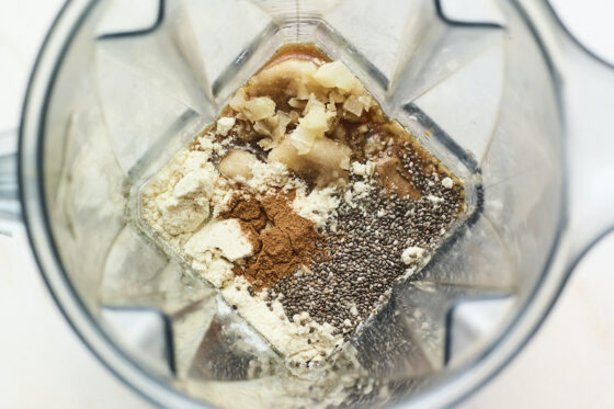 Overhead shot of blender with protein power, cauliflower, cinnamon, chia seeds and banana.