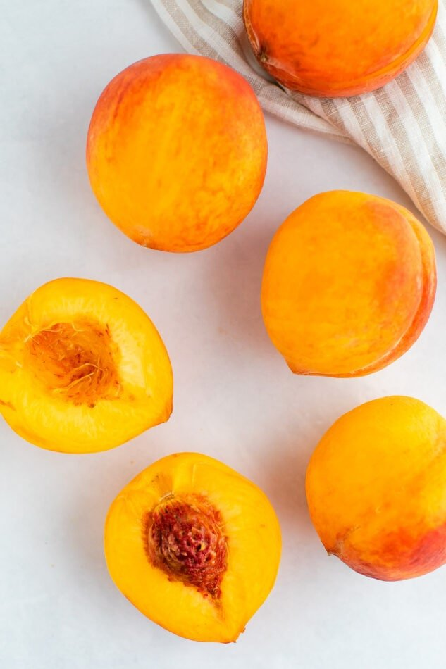 Fresh peaches on a marble surface. One is halved.