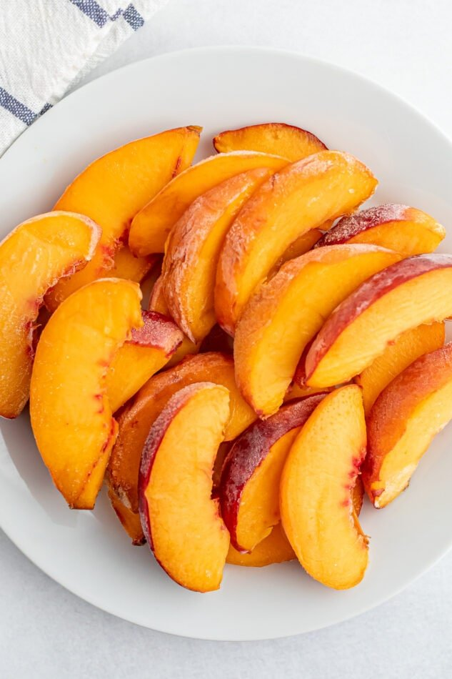 Frozen peaches on a white plate.
