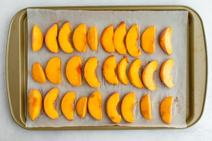 Fresh peaches in three rows on a parchment lined baking sheet, ready for freezing.