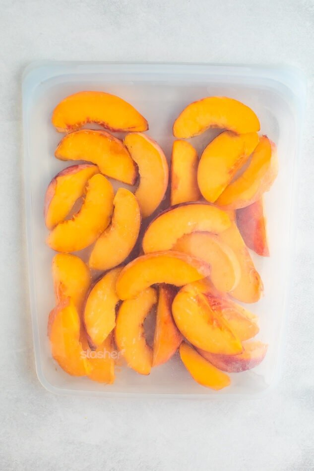 Gallon size clear Stasher bag with frozen peaches.