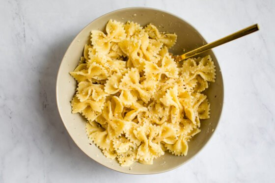 Cooked pasta being tossed in a bowl with a gold spoon.