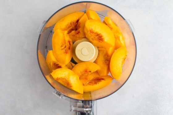 Blanched, peeled and sliced peaches in a food processor.