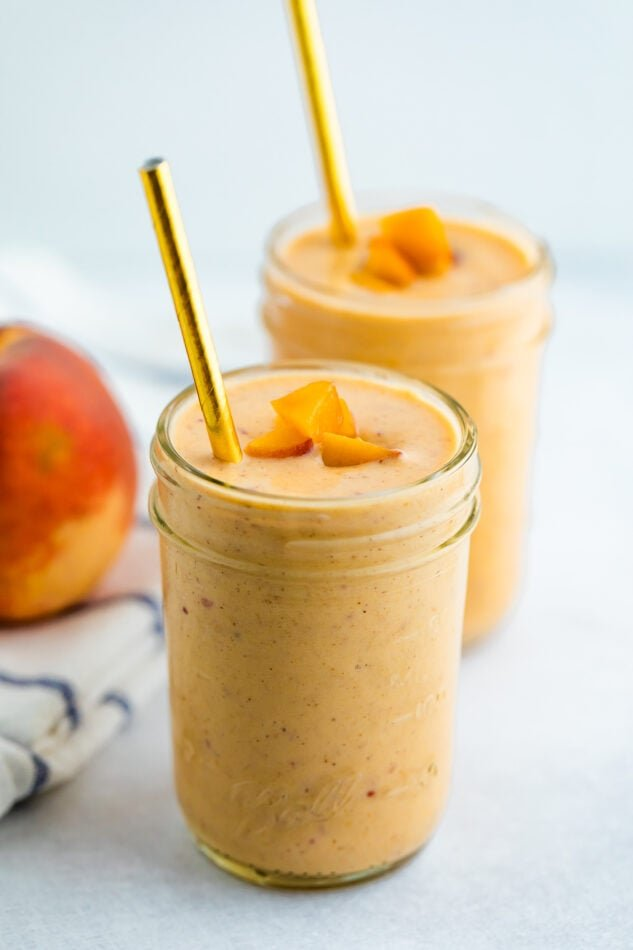 Two glass mason jars of peach smoothies. Two gold straws are in the smoothie and the smoothies are topped with chopped peached.