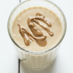 Glass with a peanut butter protein shake topped with a peanut butter drizzle.