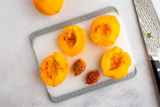 Two peaches on a cutting board with the pits removed and a knife on the right side.
