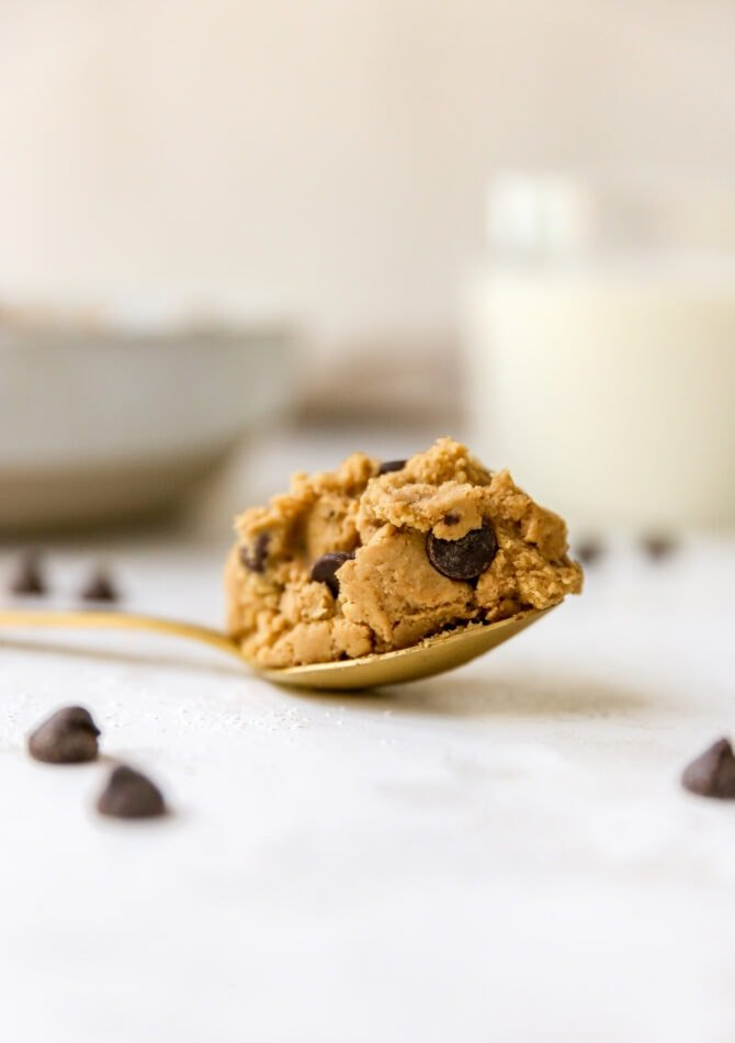A gold spoon on a white surface with a scoop of protein cookie dough.