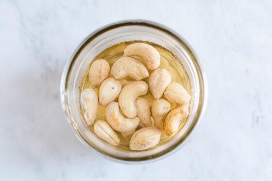 Jar of cashews soaking in water.