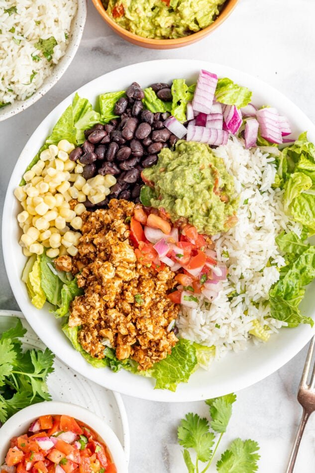 Burrito bowl made with sofritas, black beans, corn, salsa, guacamole, rice, lettuce and romaine.