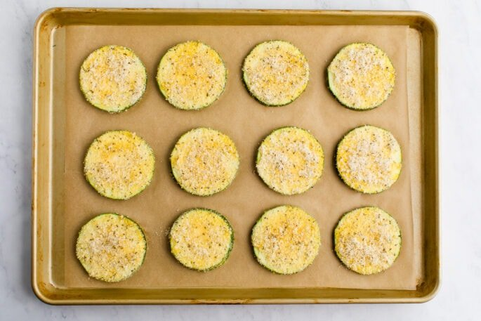Zucchini slices covered in seasoned almond flour breading on a cookie sheet.