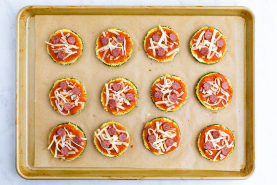 Unbaked zucchini pizza bites on a cookie tray.