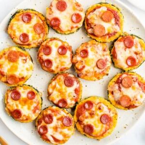 Zucchini pepperoni pizza bites on a plate.