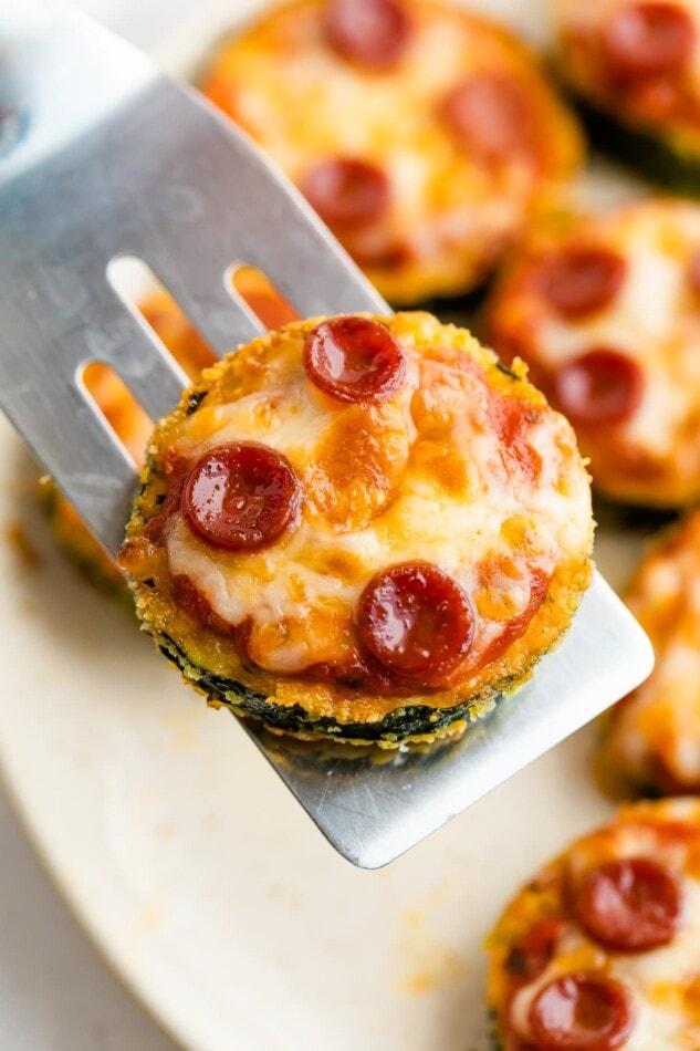 Spatula holding a zucchini pizza bite.