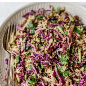 Plate with serving utensils with an apple slaw made with cabbage and quinoa.