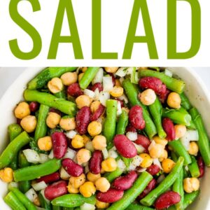 Serving bowl with three bean salad, a salad made with chickpeas, kidney beans, onion and green beans.